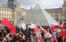 Protesters attend a demonstration in front of the glass pyramid of the Louvre museum before the opening debate on the French government's pensions reform bill at the National Assembly in Paris,Feb.17, 2020.