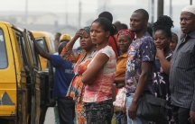 People are seen waiting for a bus at a bus-top in Lagos, Nigeria, Feb.13, 2020.