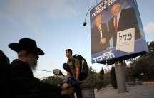 Ultra-Orthodox Jewish men walk past a Likud party election campaign banner depicting Israeli Prime Minister Benjamin Netanyahu and U.S. President Donald Trump in Jerusalem September 11, 2019.