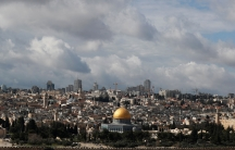 The Dome of the Rock is shown in the distance in a wide framed photograph of Jerusalem's Old City.