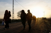 Several people are shown in shadow with the sun setting behind them and walking in a dirt road.