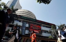 Several people are shown walking past the Bombay Stock Exchange building which has a stock ticker LED across the top.