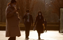 Several people are shown walking through an open area and wearing jackets and face masks.
