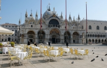 Dozen's of empty tables with white table clothes and yellow chairs are shown in St. Mark's square.