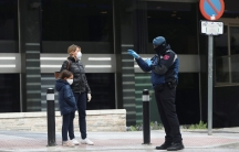 Apoliceofficer talks to a woman and child, all in face masks, outside a hotel