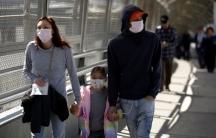 A family wearing protective face masks walks toward the US at the Paso del Norte International Border bridge.