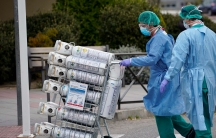 Healthcare workers wearing protective face masks bring oxygen bottles to the emergency unit at 12 de Octubre Hospital, amid the coronavirus disease (COVID-19) outbreak in Madrid, Spain March 30, 2020.