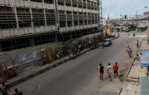 A largely abandoned street is shown with the metal wall at the base of a building empty of the normally packed market vendors.