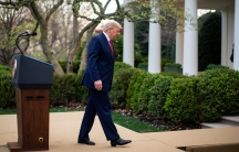 US President Donald Trump is shown wearing a blue suit and walking away from a wooden podium at the White House.