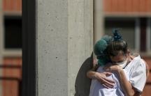 Two nurses hug each other