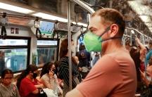 Passengers wear protective masks due to the coronavirus outbreak on a train inBangkok, March 16, 2020.