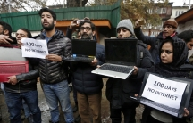 Kashmiri journalists display laptops and placards during a protest demanding restoration of internet service, in Srinagar, Nov.12, 2019.