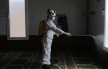 A member of theSyrian Civil Defense sanitizes inside the mosque at the Bab al-Nour internally displaced persons camp, to prevent the spread of the coronavirus disease (COVID-19) in Azaz,Syria, March 26, 2020.
