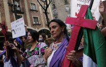 A woman holds a pink cross during a protest to mark International Women's Day at Zocalo square inMexicoCity,Mexico, March 8, 2020.