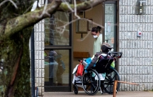 A woman opens the door to a person in a wheelchair at Pinecrest Nursing Home after several residents died and dozens of staff were sickened due to the coronavirus disease (COVID-19), in Bobcaygeon, Ontario, Canada, on March 30, 2020.