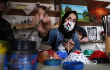 A Palestinian artist paints protective face masks to encourage people to wear them as a precaution against the coronavirus disease (COVID-19), in Gaza City, on March 30, 2020.