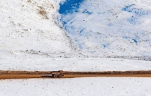 A large snowy landscape photograph depicts a single dirt road running through the lower half with a large yellow dump truck driving.