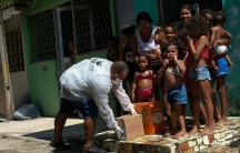 A volunteer delivers donated aid to poor families in Rio de Janeiro's slums through Single Centre of Slums (CUFA) during the coronavirus disease (COVID-19) outbreak, in Vila Kennedy slum in Rio de Janeiro, Brazil, on April 2, 2020.