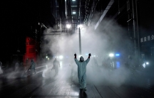 Several people are shown wearing protective clothing and spraying disinfectant in an open area in the dark of the evening.