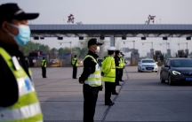 A line of police officers are shown standing in a roadway wearing protective face masks and reflective vests with toll booths in the background.