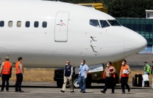 Government officials, wearing protective masks, stand next to a plane