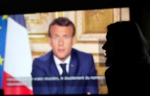 French President Emmanuel Macron is seen on a TV screen in soft focus with a person in shadow in the nearground.