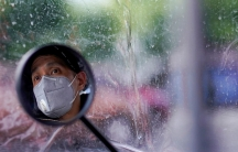 A man wearing a face mask is shown looking out and reflected in a circle bike mirror with the rest of the frame in soft focus.