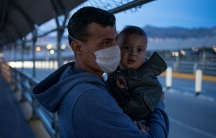 A man is shown wearing a white protective face mask while holding his young grandson.