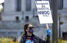 """A woman in a mask and gloves holds a sign reading """"immigrants are essential NWDC is not"""""""