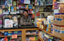 Nasim Almuntaser stands inside his packed bodega filled with products.