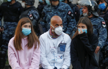 Three people wear face masks with soldiers standing behind them