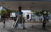 Customers wait while a fuel dispenser machine is fixed at a gas station in Caracas,Venezuela, April 23, 2020.