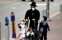 An ultra-Orthodox Jewish family wearing masks