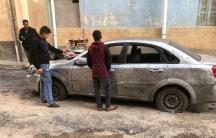Libyan boys check a damaged car after a shell fell on a residential area at Hadba al-Badri district, in Tripoli,Libya, Jan.28, 2020.