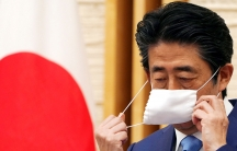 Japan's Prime Minister Shinzo Abe is shown removing a white protective face mask and wearing a blue suit with the Japanese flag in the distance.
