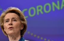 """The President of European Commission Ursula von der Leyen is shown in a close up photograph wearing pearl earings and the word """"coronavirus"""" in the background."""