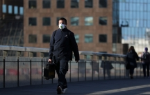 A man is shown wearing a white protective facemask and carrying a briefcase while walking.