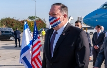 Mike Pompeo in a suit and face mask in front of a plane and the US and Israeli flags