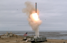 A view of a test missile launch with an American flag flying
