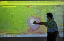 A man is shown wearing a protective face mask and pointing to an image of a cyclone projected on a screen.