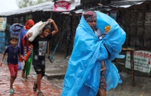 A man is shown wrapped in a blue tarp followed by several other people as heavy rains from Cylone Amphan fall.