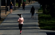 A woman wearing a protective face mask runs inMadridRiopark, during the hours allowed for individual exercise.