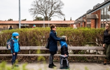 Parents with their children stand in a queue waiting to get inside Stengaard School following the coronavirus disease (COVID-19) outbreak north of Copenhagen, Denemark, April 15, 2020.