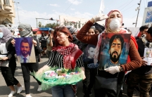 University students carry pictures of demonstrators who were killed during ongoing anti-government protests in Baghdad, March 1, 2020.