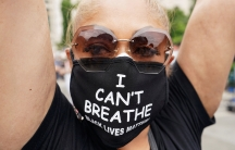 """A close of a woman with a face mask reading """"I can't breathe Black Lives Matter"""""""