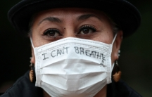"""A close up photograph of a woman wearing a white protective face mask with the words, """"I can't breathe"""" written on it."""