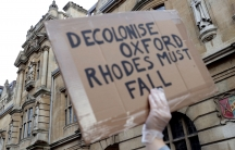 """A demonstrator's hand is seen holding a placard reading """"Decolonise Oxford/Rhodes must fall"""""""