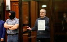 Paul Whelan is shown standing in a glass enclosed box wearing a sweater with two men standing out side of the glass wearing balaclavas.