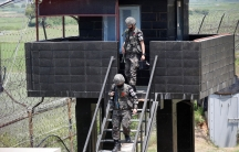 Two soldiers dressed in military fatigues and carrying weapons are shown decending a staircase from a guard tower.