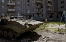 A boy walks near a Soviet-era apartment building, with a tank in the foreground
